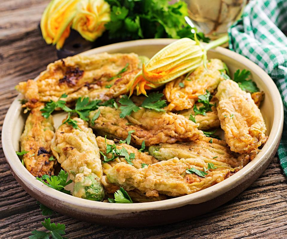 """<p>Unlike other edible flowers, zucchini blossoms don't have a floral taste. Instead, this plant has a delicate squash-like flavor and can be prepared in a variety of ways. The most common way is stuffed with cheese and deep-fried — like these incredible <a href=""""http://www.thedailymeal.com/recipes/sorbillos-ricotta-stuffed-zucchini-blossoms-recipe-0?referrer=yahoo&category=beauty_food&include_utm=1&utm_medium=referral&utm_source=yahoo&utm_campaign=feed"""" rel=""""nofollow noopener"""" target=""""_blank"""" data-ylk=""""slk:ricotta stuffed zucchini blossoms"""" class=""""link rapid-noclick-resp""""><strong>ricotta stuffed zucchini blossoms</strong></a> —and served as a tasty seasonal appetizer. You can also use shredded zucchini blossoms to serve in pasta, on top of <a href=""""https://www.thedailymeal.com/best-recipes/best-pizza-recipes-and-pizza-cooking-ideas?referrer=yahoo&category=beauty_food&include_utm=1&utm_medium=referral&utm_source=yahoo&utm_campaign=feed"""" rel=""""nofollow noopener"""" target=""""_blank"""" data-ylk=""""slk:pizza"""" class=""""link rapid-noclick-resp"""">pizza</a> or stuffed inside quesadillas.</p>"""