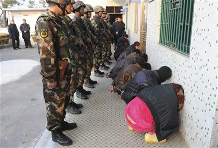 Paramilitary policemen guard suspects during a raid where three tonnes of crystal meth were seized at Boshe village, Lufeng