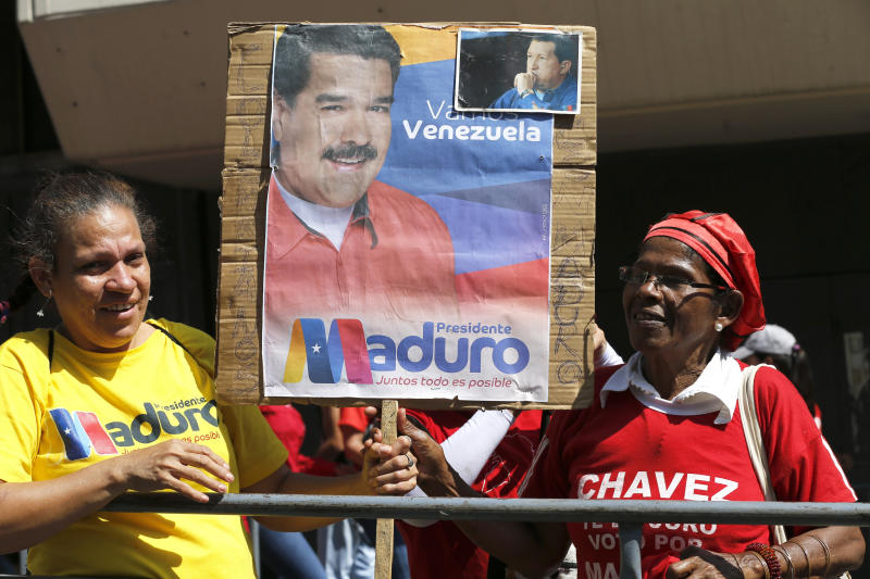Supporters of Venezuela's President Nicolas Maduro hold a poster of him outside the Supreme Court where he is being sworn-in for another term in Caracas, Venezuela, Thursday, Jan. 10, 2019. Maduro was sworn in to a second term amid international calls for him to step down and a devastating economic crisis. (AP Photo/Ariana Cubillos)