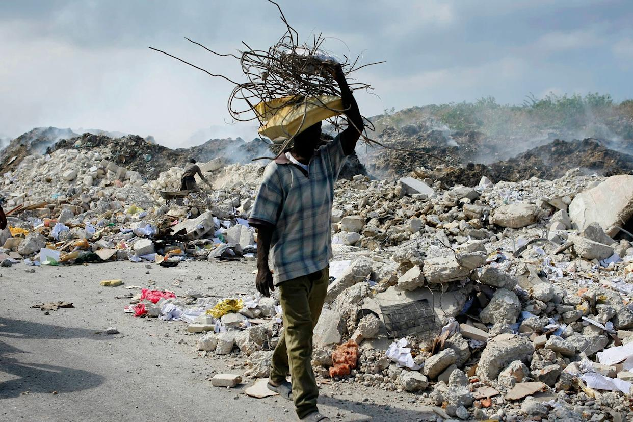A man carries a bundle of metal bars salvaged from the rubble of collapsed buildings in Port-au-Prince, Haiti, on Jan. 17, 2010.