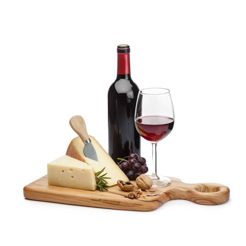 Cheese and wine: cutting board with cheese slices, grape and walnuts isolated on white background. A red wine bottle and a wineglass are behind the cheese tray. Useful copy space available for text and/or logo. High key DSRL studio photo taken with Canon EOS 5D Mk II and Canon EF 100mm f/2.8L Macro IS USM.