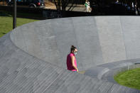A visitor looks over inscriptions on the walls of the Memorial to Enslaved Laborers at the University of Virginia in Chrlottesville, Va., Friday Oct. 23, 2020. Devon Henry's company, Team Henry Enterprises, was the general contractor for the recently completed Memorial that honors the enslaved people who built and sustained the Thomas Jefferson-founded university. (AP Photo/Steve Helber)