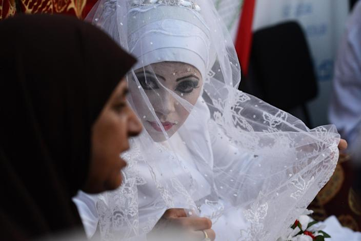 Heba Fayad, a 23-year-old Palestinian woman, listens to her mother Nabila (L) during her wedding ceremony at a UN school school in Gaza City's Shati refugee camp on August 13, 2014 (AFP Photo/Roberto Schmidt)