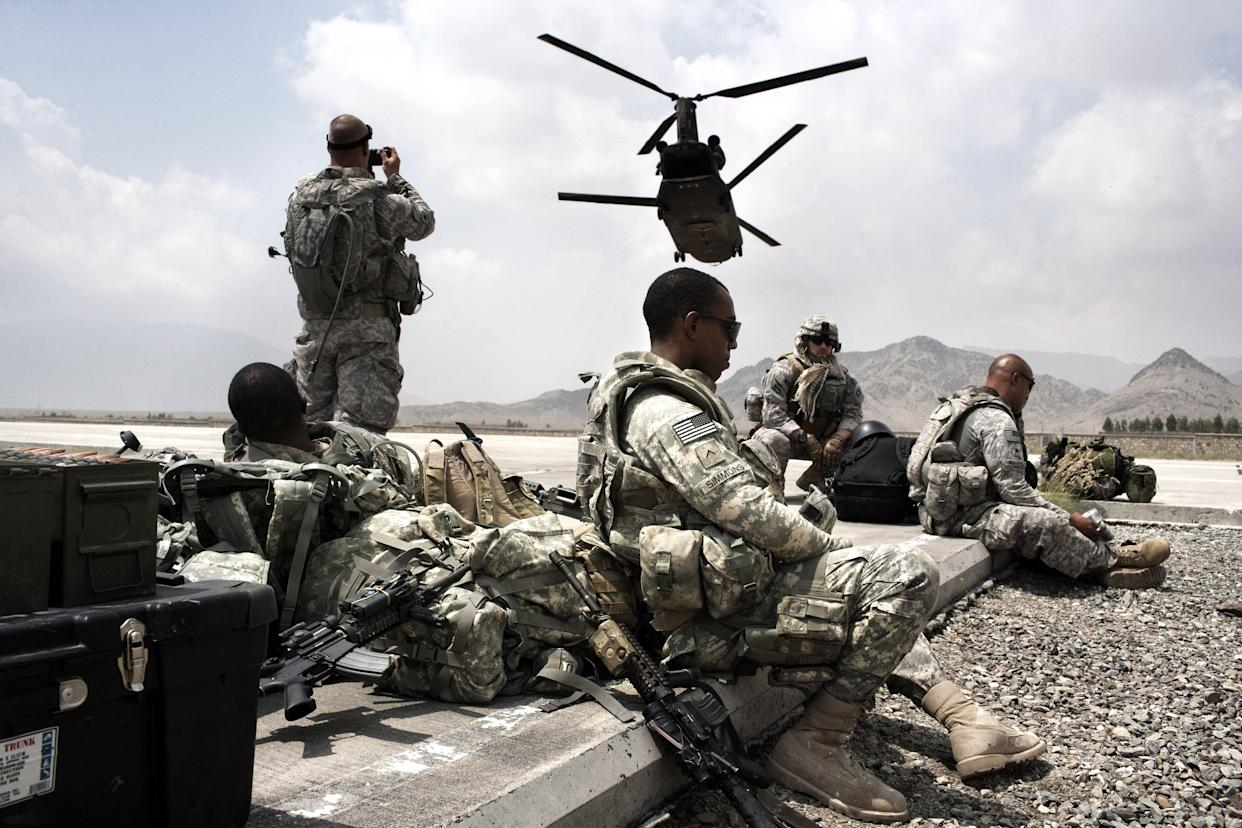 US Army soldiers from the Alpha Company 1/121 Infantry (L), 48th BCT and US Army Embedded Training Team and Human Terrain Team wait on a landing strip for an helicopter to fly to Spera District Center (DC) on August 18, 2009 in Camp Parsa, Nader Shah Kot, Khost Province, Afghanistan. (Marco Di Lauro/Getty Images)
