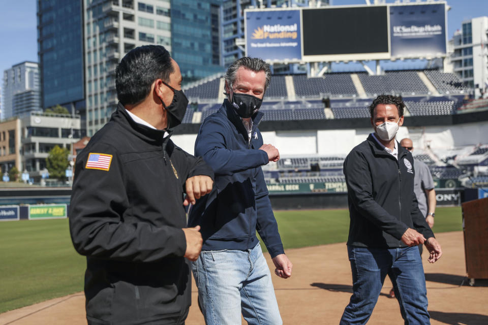 FILE - In this Feb. 8, 2021, file photo, California Governor Gavin Newsom, center, bumps elbows with San Diego Mayor Todd Gloria after a news conference at Petco Park, which will host a vaccination site in a parking lot next to the ballpark in San Diego. Newsom's weeklong tour of vaccination sites has taken on the feel of a campaign swing as the likelihood increases that he'll face a recall election. (Sandy Huffaker/The San Diego Union-Tribune via AP, Pool, File)