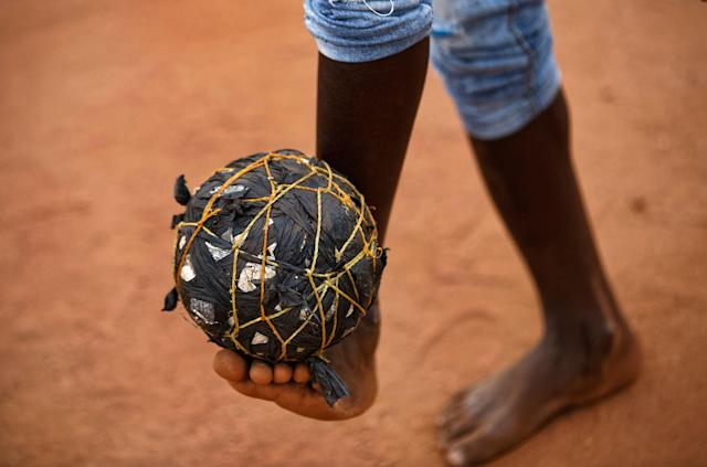 <p>A South Sudanese refugee boy plays with a ball made from plastic bags and string, on the day that much of the world watch the 2017 Champions League final, on a dirt pitch in Bidi Bidi refugee camp in northern Uganda, Saturday, June 3, 2017. Bidi Bidi is a sprawling complex of mud-brick houses that is now the world's largest refugee settlement holding some of those who fled the civil war in South Sudan, which has killed tens of thousands and driven out more than 1.5 million people in the past three years, creating the world's largest refugee crisis. (Photo: Ben Curtis/AP) </p>