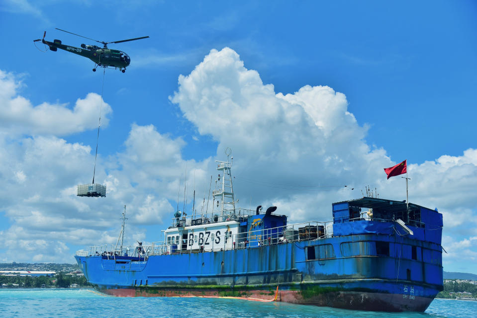 A helicopter drops cargo containing oil pumping equipment onto the deck of the FV Lu Rong Yuan Yu, a Chinese-flagged fishing vessel that has run aground, at Pointe-aux Sables, Port-Louis, Mauritius, Tuesday March 9 2021. Workers in Mauritius have begun pumping 130 tons of fuel from a Chinese fishing vessel that ran aground on a coral reef on the Indian Ocean island's west coast on Sunday. Local newspaper L'Express reported that the grounded ship has spilled a small amount of fuel into the ocean, but its hull remains intact. (Beekash Roopun/L'express Maurice via AP)