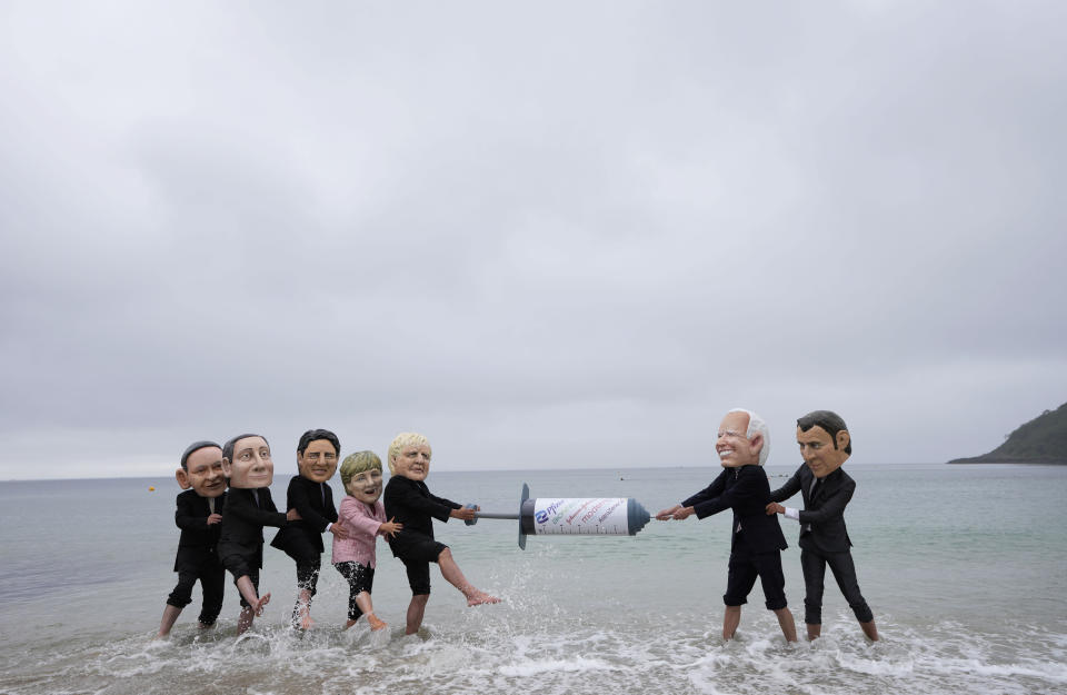 Activists wearing giant heads of the G7 leaders tussle over a giant COVID-19 vaccine syringe during an action of NGO's on Swanpool Beach in Falmouth, Cornwall, England, Friday, June 11, 2021. Depicted from left to right, Japan's Prime Minister Yoshihide Suga, Italy's Prime Minister Mario Draghi, Canadian Prime Minister Justin Trudeau, German Chancellor Angela Merkel, British Prime Minister Boris Johnson, U.S. President Joe Biden and French President Emmanuel Macron. (AP Photo/Kirsty Wigglesworth)