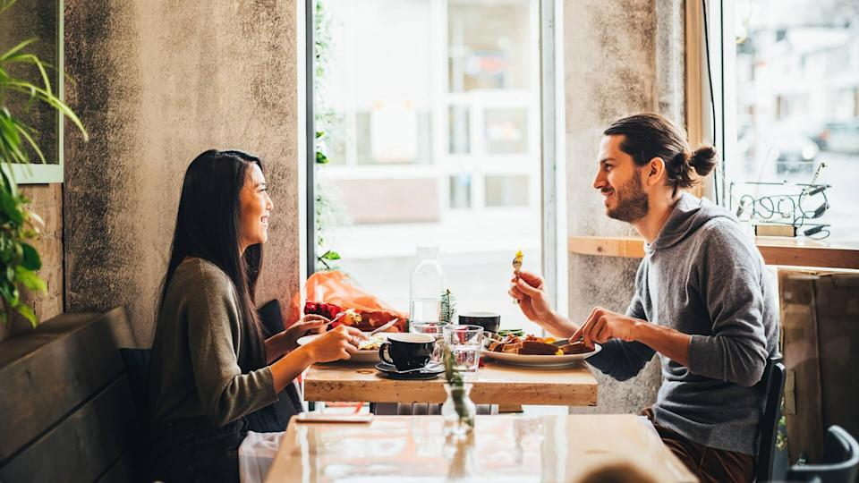 Young interracial couple on a date at the Bistro restaurant on Valentine's Day holiday.