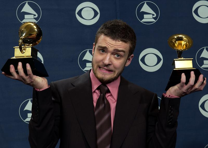 Justin Timberlake reacts as he holds the awards he won for best male pop vocal performance and best pop vocal album at the 46th Annual Grammy Awards, Sunday, Feb. 8, 2004, in Los Angeles. (AP Photo/Reed Saxon)