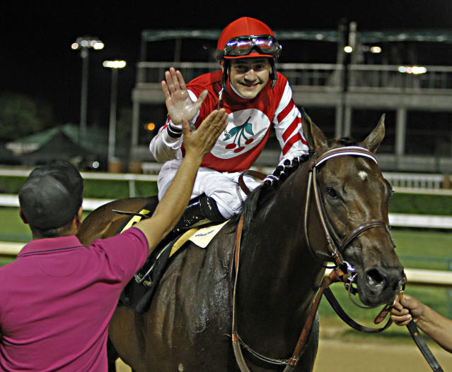 Jockey Brian Hernandez Jr.. top, celebrates with a groom after his mount, Embellishing Bob, was declared the winner of the Derby Trial horse race following the disqualification of winner Bayern at Churchill Downs in Louisville, Ky., Saturday, April 26, 2014. (AP Photo/Garry Jones)