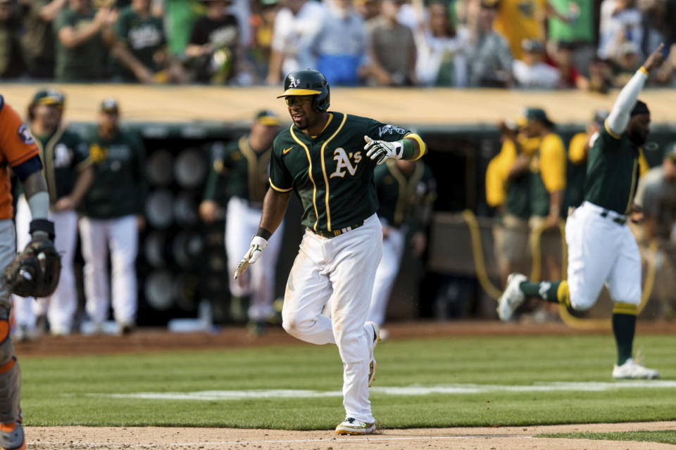 Oakland Athletics' Elvis Andrus collapses with an injury after scoring against the Houston Astros in the ninth inning of a baseball game in Oakland, Calif., Saturday, Sept. 25, 2021. The Athletics won 2-1. (AP Photo/John Hefti)