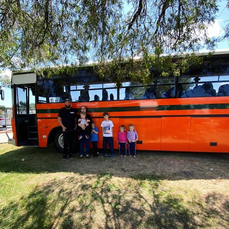Jo and Gary Pascoe and their five children outside their bright orange school bus