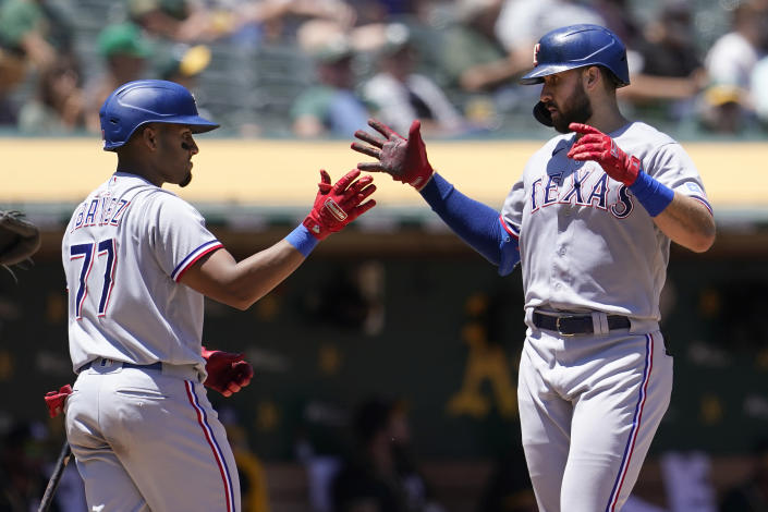 Texas Rangers' Joey Gallo, right, is congratulated by Andy Ibanez, left, after hitting a two-run home run during the fifth inning of a baseball game against the Oakland Athletics in Oakland, Calif., Thursday, July 1, 2021. (AP Photo/Jeff Chiu)