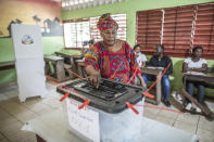 A woman votes at the Boulbinet Deaf School in Conakry, Guinea, Sunday Oct. 18, 2020. Guinean President Alpha Conde is seeking to extend his decade in power, facing off against his longtime rival Cellou Dalein Diallo for the third time at the polls. (AP Photo/Sadak Souici)