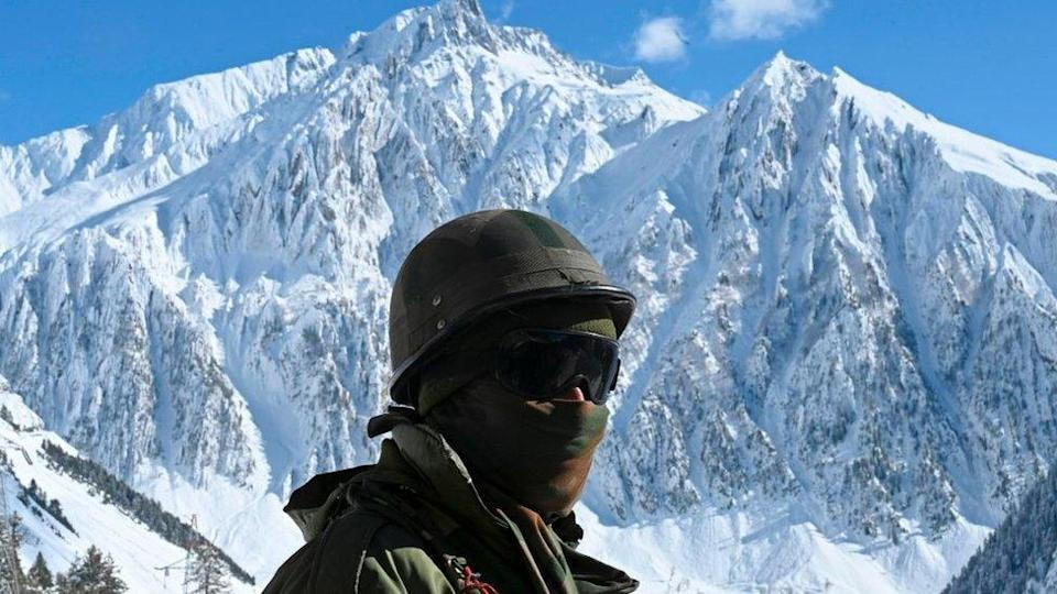 An Indian army soldier stands on a snow covered road that connects Srinagar to the union territory of Ladakh, bordering China