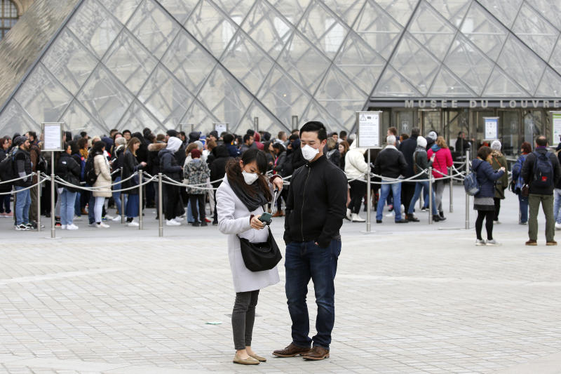 PARIS, FRANCE - MARCH 04: A couple wearing protective masks takes a selfie in front of the Louvre Museum as the museum was closed for a staff meeting about the coronavirus outbreak on March 4, 2020 in Paris, France. Due to a sharp increase in the number of cases of coronavirus (COVID-19) declared in Paris and throughout France, several sporting, cultural and festive events have been postponed or canceled. The epidemic has exceeded 3,000 dead for more than 86,000 infections in sixty countries. In France, 130 cases are now confirmed, in 13 regions in total. (Photo by Chesnot/Getty Images)