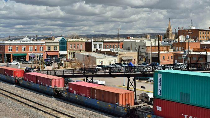 """""""Laramie, Wyoming, USA - March 30, 2013: A cyclist on an overpass over a rail yard in Laramie with other people in the background."""