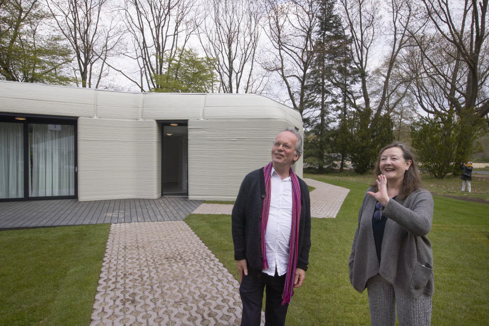 Tenants Elize Lutz, right, and Harrie Dekkers' new home, rear, is a 94-square meters (1,011-square feet) two-bedroom bungalow resembling a boulder with windows in Eindhoven, Netherlands, Friday, April 30, 2021. The fluid, curving lines of its gray walls look natural. But they are actually at the cutting edge of housing construction in the Netherlands and around the world. They were 3D printed at a nearby factory. (AP Photo/Peter Dejong)