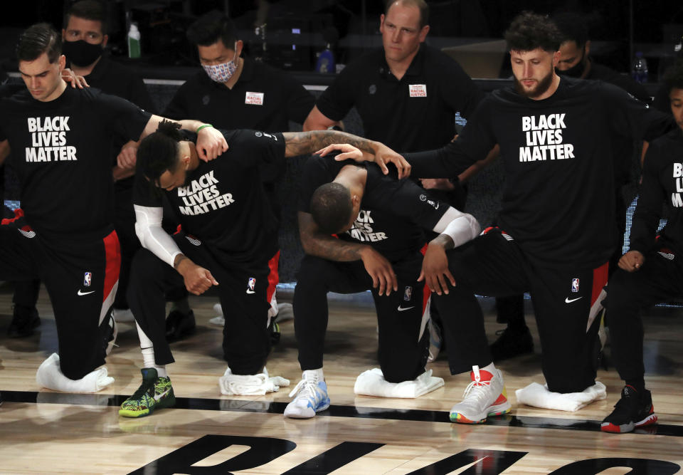 Portland Trail Blazers' Damian Lillard, second from right, the kneels with teammates and coaches during the national anthem before an NBA basketball game against the Memphis Grizzlies, Friday, July 31, 2020, in Lake Buena Vista, Fla. (Mike Ehrmann/Pool Photo via AP)
