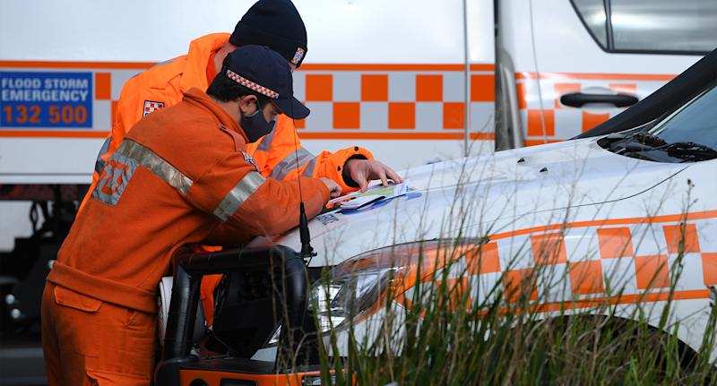 Two SES personnel examine a map before continuing search for William Wall.