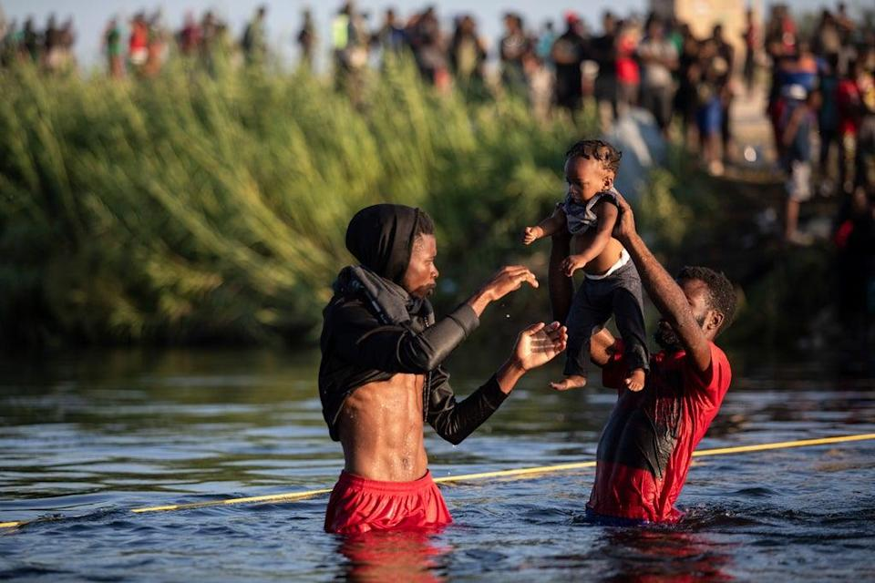 Men lift a baby over the waters of the Rio Grande river as migrants, many from Haiti, wade across the from Del Rio, Texas, to return to Ciudad Acuña, Mexico, Monday, 20 September 2021, to avoid deportation from the US (AP)
