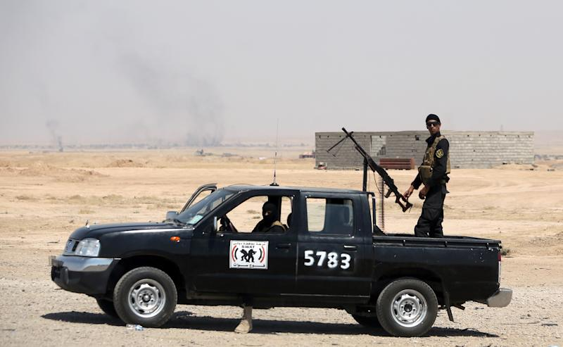 Iraqi security forces guard the main road between Baghdad and Kirkuk on September 3, 2014