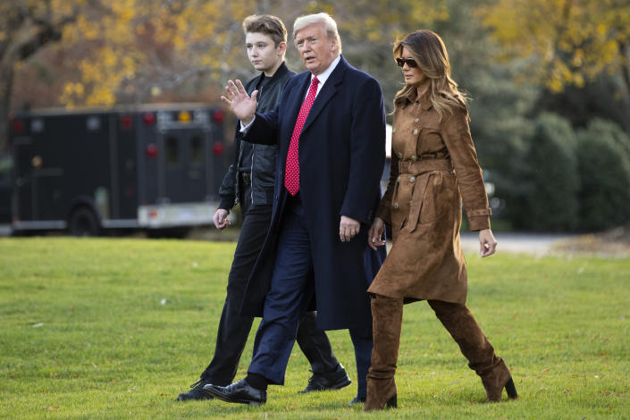 FILE- In this Nov. 26, 2019, file photo, President Donald, first lady Melania Trump, and Barron Trump, walk to board Marine One on the South Lawn of the White House, in Washington. Melania Trump is quietly forging her way through President Donald Trump's impeachment. (AP Photo/ Evan Vucci, File)