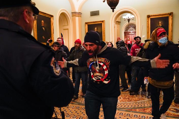 Protesters gesture to U.S. Capitol Police in the hallway outside of the Senate chamber at the Capitol in Washington, Wednesday, Jan. 6, 2021, near the Ohio Clock. At center is Doug Jensen of Des Moines, Iowa who was later arrested and charged, the Des Moines Register reported.