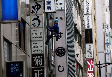 Worker cleans a window of a building at a shopping district in Tokyo