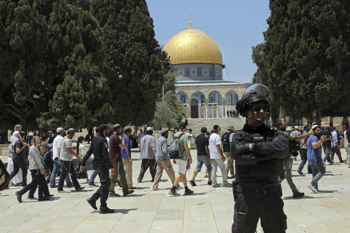 An Israeli police officer stands guard as Jewish men visit the Dome of the Rock Mosque in the Al Aqsa Mosque compound, during the annual mourning ritual of Tisha B'Av (the ninth of Av) -- a day of fasting and a memorial day, commemorating the destruction of ancient Jerusalem temples, in the Old City of Jerusalem, Sunday, July 18, 2021. (AP Photo/Mahmoud Illean)