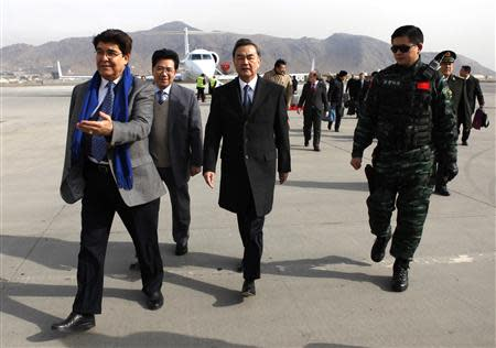 Chinese Foreign Minister Wang Yi (C) arrives at the International Airport in Kabul February 22, 2014. REUTERS/Mohammad Ismail
