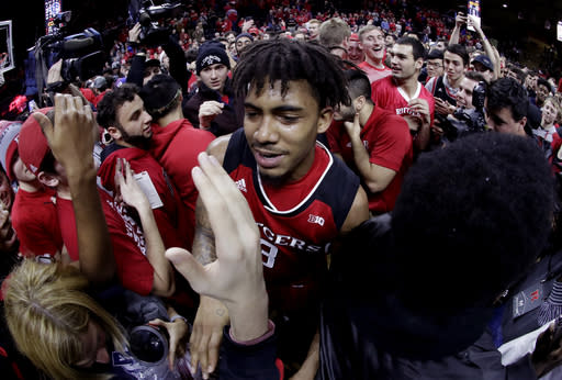 "Rutgers guard <a class=""link rapid-noclick-resp"" href=""/ncaaf/players/257707/"" data-ylk=""slk:Corey Sanders"">Corey Sanders</a> is mobbed by fans after upsetting Seton Hall 71-65 in Piscataway, N.J. (AP Photo)"