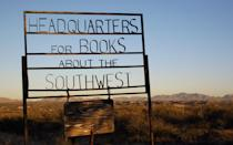 """<p>If you think diving into a great novel is an escape, try finding your way to the <a rel=""""nofollow noopener"""" href=""""https://www.facebook.com/singingwindbookshop/"""" target=""""_blank"""" data-ylk=""""slk:Singing Wind Bookshop"""" class=""""link rapid-noclick-resp"""">Singing Wind Bookshop</a>, four and half miles north of small-town Benson, Arizona, surrounded by the desert plains of San Pedro Valley. Opened more than 40 years ago by Winn Bundy, this bookstore—an old ranch house—is as remote as they come, and that's half the fun. Specializing in books about and authors of the Southwest—including the great Edward Abbey, an early customer—Singing Wind Bookshop is truly one of a kind. """"It's an honor to be a customer at her shop,"""" Tucson author Bill Broyles told The Arizona Republic. """"It's like being invited to a cave of hidden treasure, or the inner sanctum.""""</p>"""