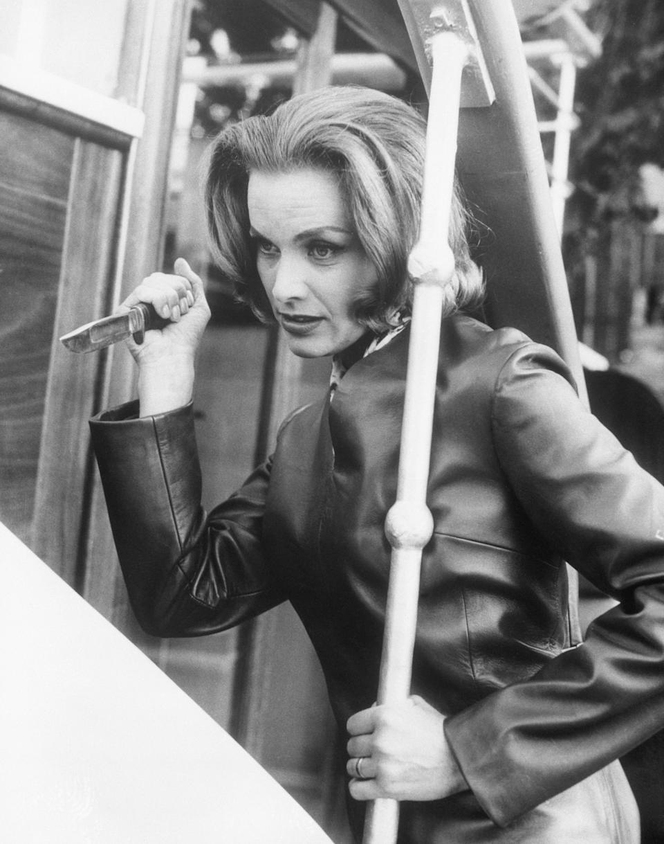 """(Original Caption) 2/27/1963-London, England- Dressed in a leather suit and wielding a knife, Honor Blackman, looks dangerous, while tilling part of an undercover agent in a television series. The British actress says her portrayal in the British ABC-TV series, """"The Avengers,"""" it's a chance to throw in a bit of the real her...she's all woman, but has a pretty tough streak too."""