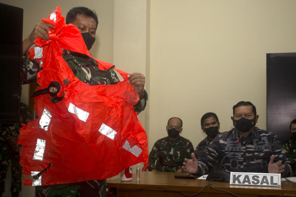 THIS CORRECTS THE NAME OF THE PHOTOGRAPHER TO LISNAWATI - A military officer display a life jacket found in the waters during a search for the Indonesian Navy submarine KRI Nanggala at Ngurah Rai Military Air Base in Bali, Indonesia on Sunday, April 25, 2021. Indonesia's military on Sunday officially admitted there was no hope of finding survivors from the submarine that sank and broke apart last week with 53 crew members aboard, and that search teams had located the vessel's wreckage on the ocean floor. (AP Photo/Firdia Lisnawati)