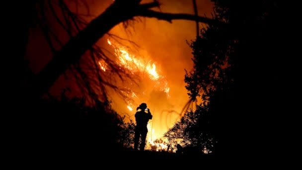 PHOTO: A firefighter takes a cell phone picture during a wildfire, Dec. 16, 2017, in Montecito, Calif. (Chris Carlson/AP)