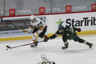 Minnesota Wild's Carson Soucy (21) tries to knock the puck away from Vegas Golden Knights' Ryan Reaves (75) in the third period of an NHL hockey game Monday, March 8, 2021, in St. Paul, Minn. (AP Photo/Stacy Bengs)