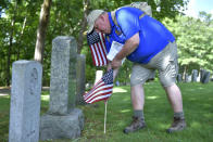"""Craig DeOld, a retired Army Captain, and commander of the Boston Police VFW, replaces flags at veteran's graves Thursday, May 27, 2021, in the Fairview Cemetery in Boston. After more than a year of isolation, American veterans are embracing plans for a more traditional Memorial Day. """"We're breathing a sigh of relief that we've overcome another struggle, but we're also now able to return to what this holiday is all about — remembering our fallen comrades."""" (AP Photo/Josh Reynolds)"""