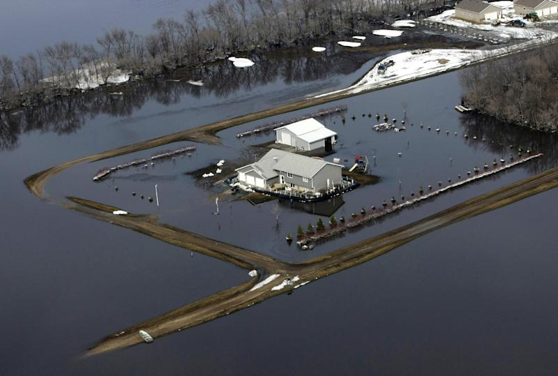 In this March 29, 2009 file photo, a house sits isolated by flood waters from the Red River south of Fargo, N.D. Federal Emergency Management Agency officials are frustrated by the number of people in the Red River Valley and elsewhere in North Dakota who don't have flood insurance, citing the state's history of presidential disaster declarations. The number of insurance policies in flood-prone Fargo and Cass County, where residents have battled flooding along the Red River and its tributaries for six of the last eight years, dropped by more than 40 percent from 2011 to 2012, FEMA officials said. (AP Photo/Charles Rex Arbogast)