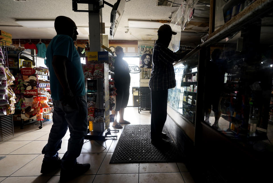 Customers shop in a convenience store that opened with no electricity after the effects the effects of Hurricane Ida knocked out power in the area, Monday, Aug. 30, 2021, in Nhew Orleans, La. (AP Photo/Eric Gay)