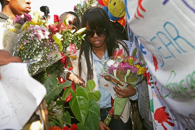 PRETORIA, SOUTH AFRICA - JUNE 27: Some of former South African President Nelson Mandela's grand children and great-grandchildren collect flowers left by supporters outside the Mediclinic Heart Hospital where Mandela is being treated for a recurring lung infection on June 27, 2013 in Pretoria, South Africa. President Jacob Zuma is scheduled to make an announcement to the country at noon today. (Photo by Chip Somodevilla/Getty Images)