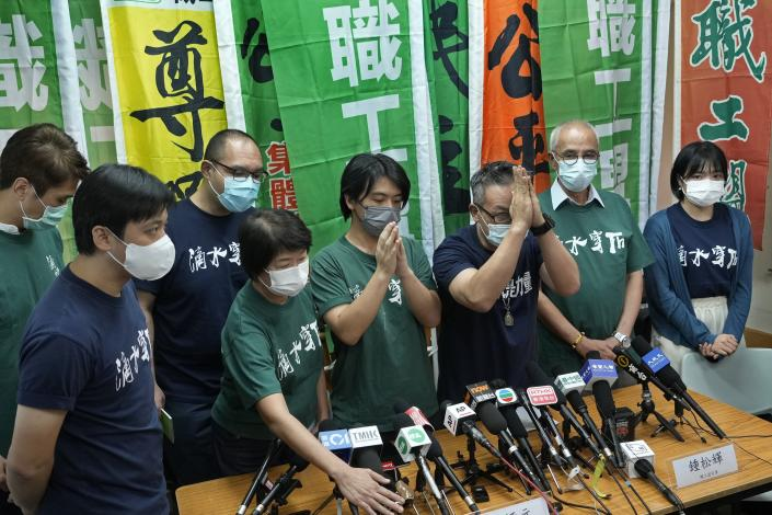 """Hong Kong Confederation of Trade Unions President Joe Wong Nai-yuen, third from right, with deep blue T-shirt, gestures while posing for a photo with other members before a news conference on the possibility of disbandment in Hong Kong Sunday, Sept. 19, 2021. Hong Kong's biggest opposition trade union said Sunday it would disband, following concerns for """"members' personal safety."""" (AP Photo/Vincent Yu)"""