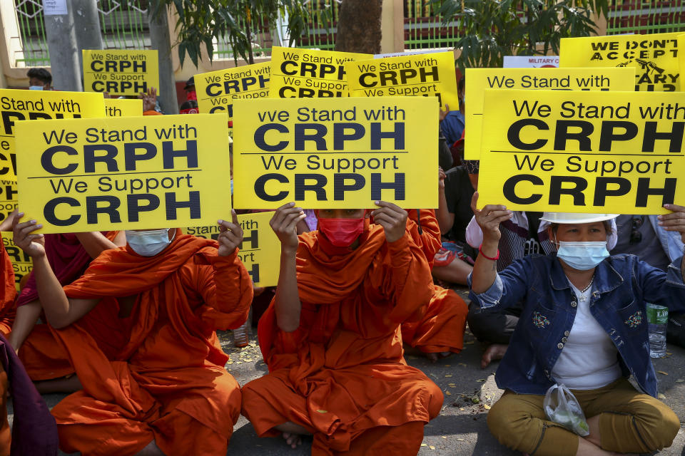 "Buddhist monks display placards during an anti-coup protest in Mandalay, Myanmar, Saturday, Feb. 27, 2021. Myanmar security forces cracked down on anti-coup protesters in the country's second-largest city Mandalay on Friday, injuring at least three people, two of whom were shot in the chest by rubber bullets and another who suffered a wound on his leg. ""CRPH"" in the placards stand for ""Committee Representing Pyidaungsu Hluttaw."" (AP Photo)"