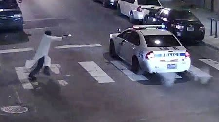 A still image from surveillance video shows a gunman (L) approaching a Philadelphia Police vehicle in which Officer Jesse Hartnett was shot shortly before midnight January 7, 2016 in Philadelphia, Pennsylvania this Philadelphia Police Department image released on January 8, 2016.  REUTERS/Philadelphia Police Department/Handout