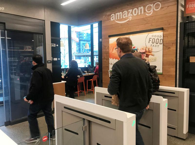 FILE PHOTO: A customer walks out of the Amazon Go store, without needing to pay at a cash register due to cameras, sensors and other technology that track goods that shoppers remove from shelves and bill them automatically after they leave, in Seattle