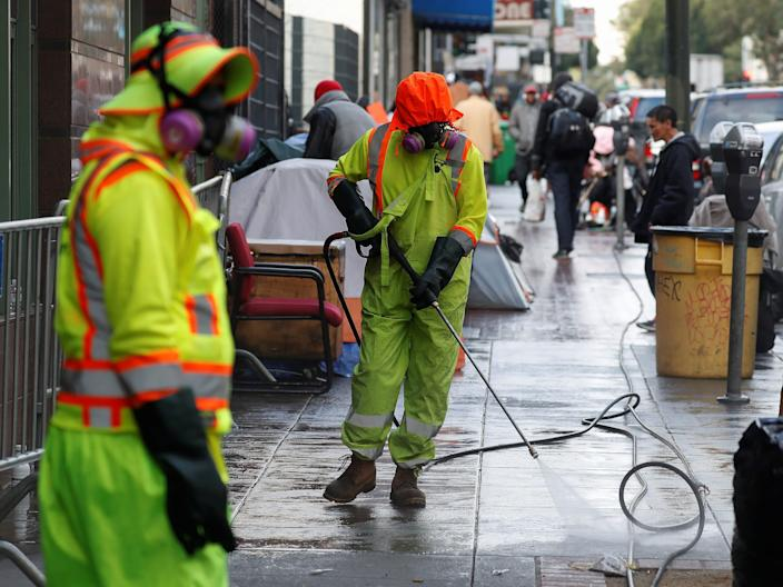 Workers sanitize streets where homeless people are living in the Tenderloin district of San Francisco, California, March 20, 2020.