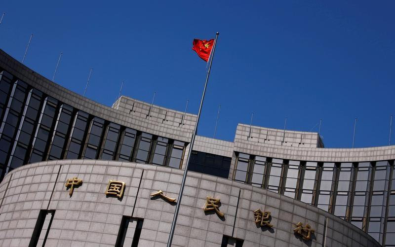 A Chinese national flag flutters outside the headquarters of the People's Bank of China, the Chinese central bank, in Beijing, China