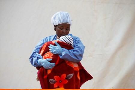 FILE PHOTO: Rachel Kahindo, an Ebola survivor working as a caregiver to babies who are confirmed Ebola cases, holds an infant outside the red zone at the Ebola treatment centre in Butembo