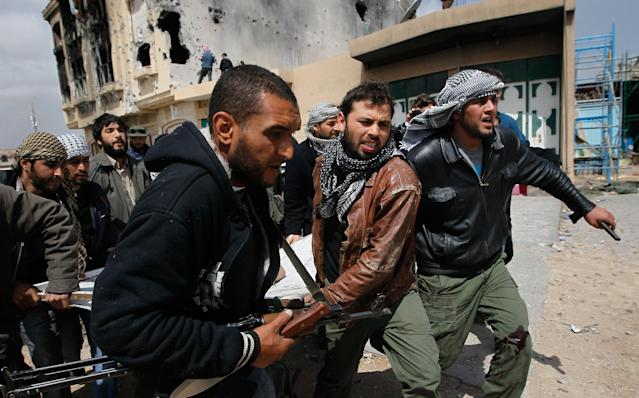 <p>Libyan rebel fighters carry out a comrade wounded during an effort to dislodge some ensconced government loyalist troops who were firing on them from a building (background) during house-to-house fighting on Tripoli Street in downtown Misrata April 20, 2011 in Misrata, Libya. (Photo by Chris Hondros/Getty Images) </p>